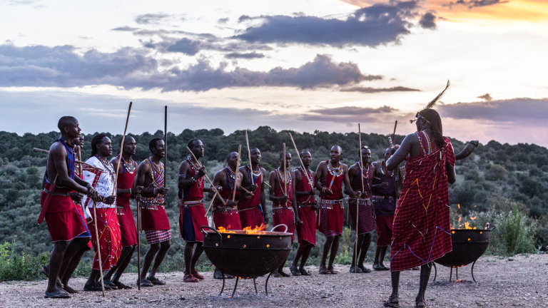 Maasai warriors at Angama Mara sunset boma