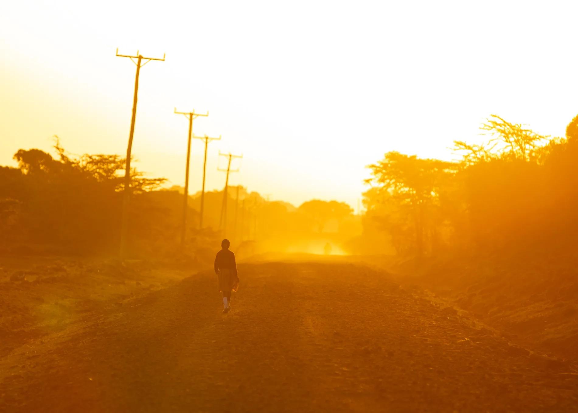 Maasai kid walking on road
