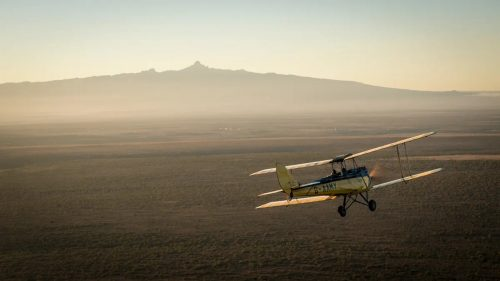 Segera's G-AAMY biplane heading towards Mount Kenya