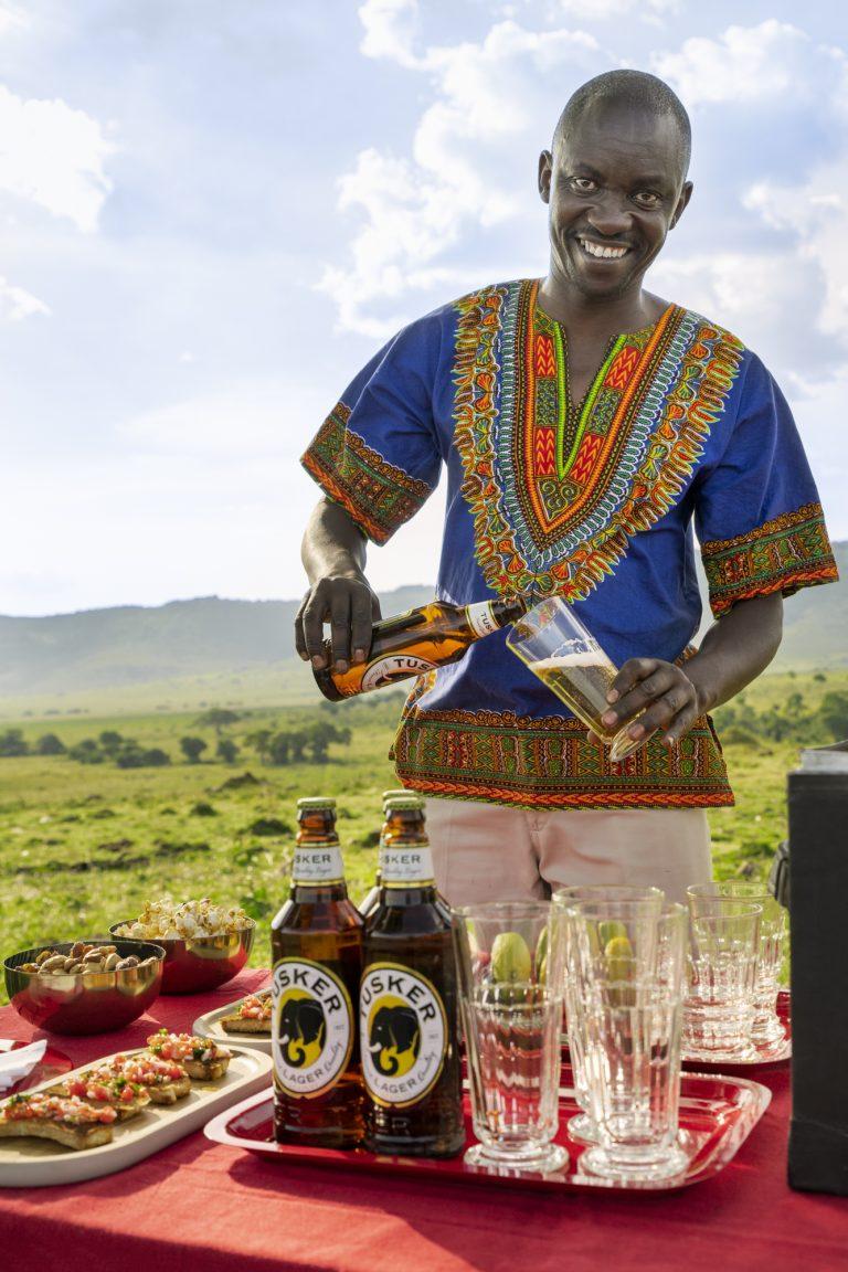 Butler Wikie serving drinks at sundowner in the Maasai Mara