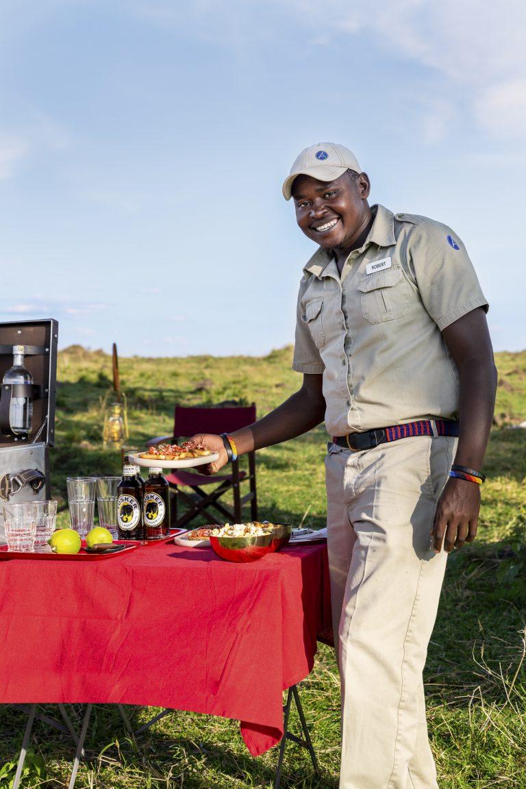Guide Robert serving bitings at sundowner in the Maasai Mara