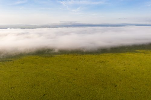 Like a massive wave, the morning fog envelops the Mara