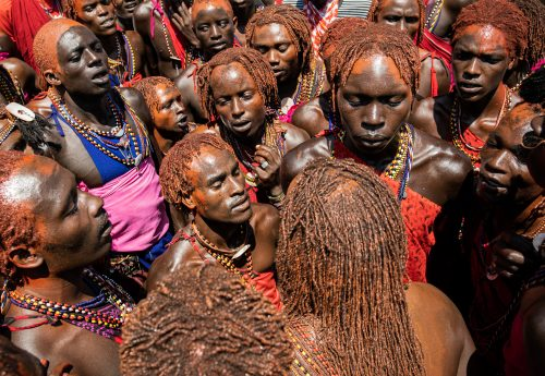 Red ochre painted young Maasai warriors chanting together
